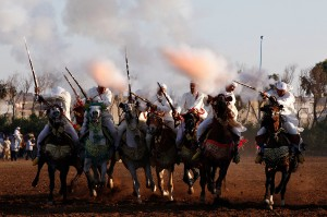 Horse riders perform with guns during the El-Jadida International Horse Show in El-Jadida
